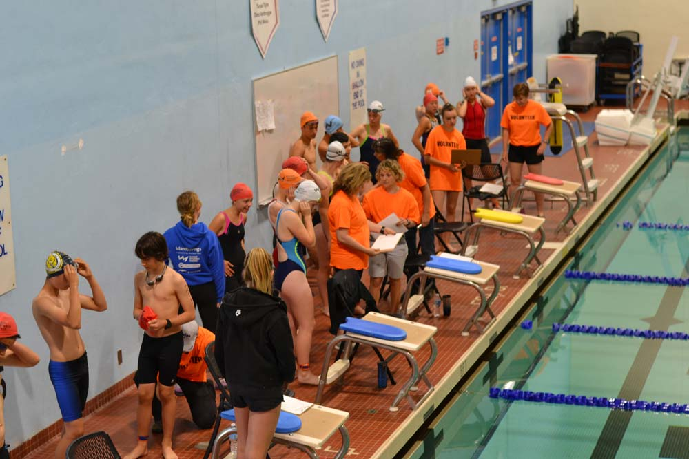 Youth triathlon participants line up along the pool edge