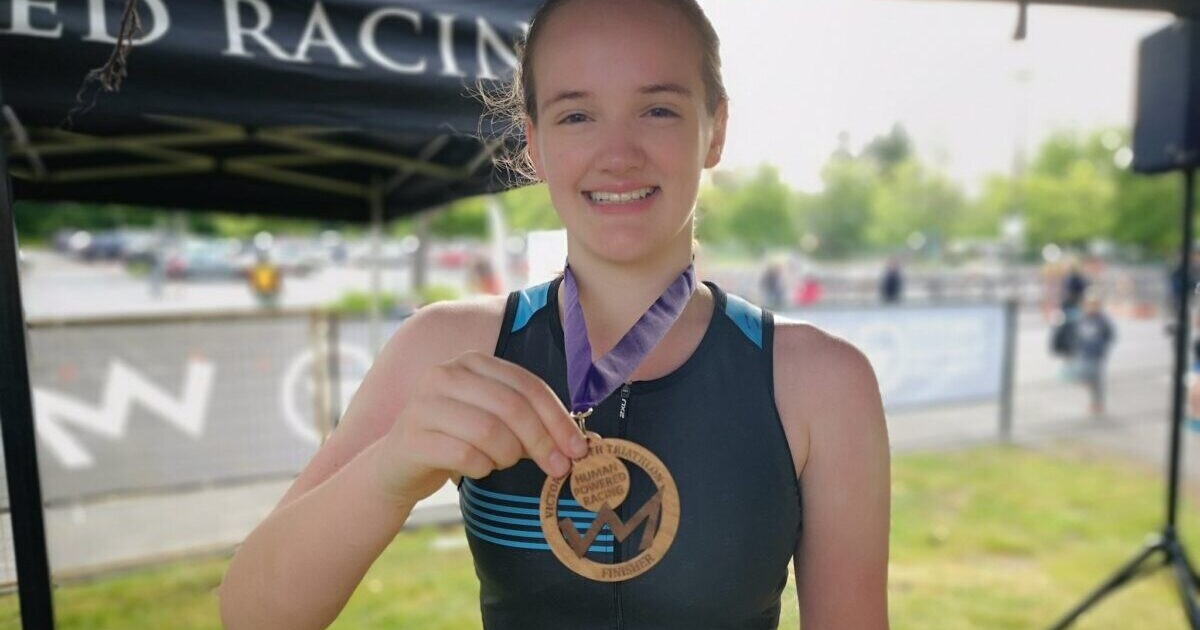 Lauren Harrison holds up her medal at the Victoria Youth Triathlon.