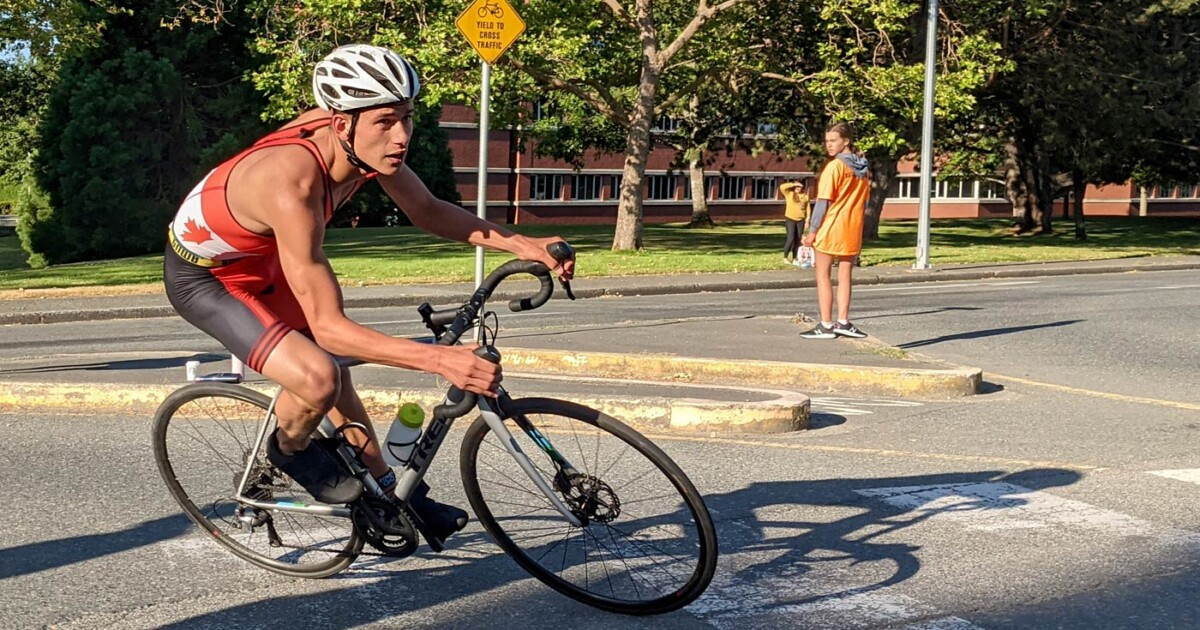 A racer leans into the corner coming into the transition area going very fast.
